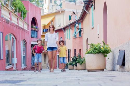 Βιλφράνς: Μητέρα και δύο παιδιά περπατώντας χέρι-χέρι σε έναν πολύχρωμο δρόμο στη Βιλφράνς. Γαλλία.