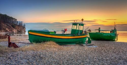 Γκντύνια: Ψαρόβαρκες στην παραλία της Βαλτικής Θάλασσας κατά την ανατολή στην Γκντύνια. Πολωνία.