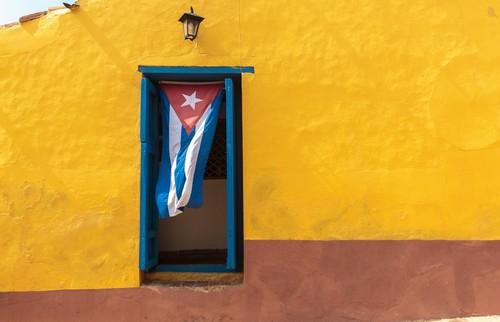 Ίσλα Δεν Λα Χουβεντούδ: Κίτρινος τοίχος, μπλε παράθυρο και για κουρτίνα ...η σημαία της χώρας. Ίσλα Δε Λα Χουβεντούδ. Κούβα.