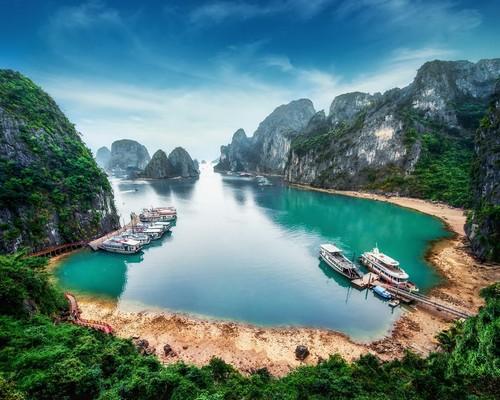 Κόλπος Χαλόνγκ: Τουριστικά πλοιάρια που επιπλέουν ανάμεσα σε ασβεστολιθικά βράχια στον μακρύ κόλπο της Νότιας Κίνας και νοτιοανατολικά της θάλασσα του Βιετνάμ. Κόλπος Χαλόνγκ. Βιετνάμ.
