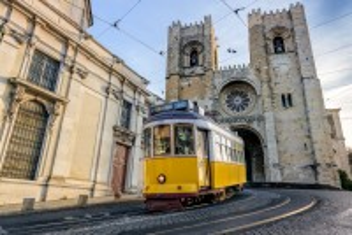 Λισαβόνα: Το κίτρινο τραμ περνά μπροστά από τον καθεδρικό ναό της Σάντα Μαρία. Λισσαβώνα. Πορτογαλία.