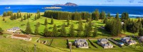 Νησί Νόρφολκ: Νότιος Ειρηνικός Ωκεανός. Γήπεδο γκολφ στο Norfolk Island, μέσα στα πεύκα του νησιού. Στο προσκήνιο βρίσκονται κτίρια από την περίοδο καταδίκων της δεκαετίας του 1820. Νησί Νόρφολκ. Αυστραλία