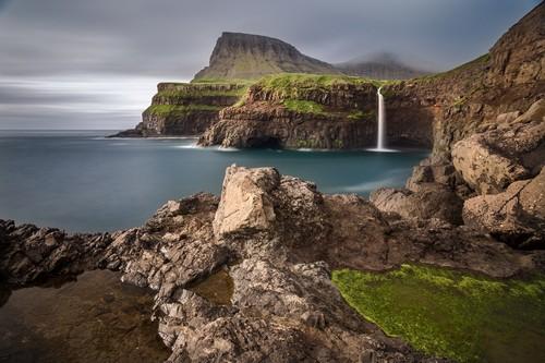 Νησιά Φερόε: Καταράκτες στο χωριό Γκασανταλούρ σε τοπίο που κυριαρχείται από απόκρυμνα βουνά.Νησιά Φερόε. Δανία.