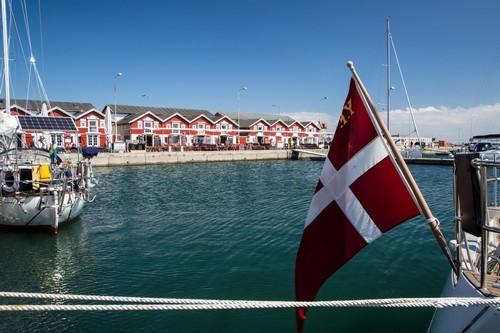 Σκάγκεν: Οι πόλεις marinaharbour με τυπικά κόκκινα ξύλινα κτίρια και πλοία της Δανίας. Μπλε ουρανός και ωραίο νερό. Δανική σημαία μπροστά ... Σκάγκεν. Γιουτλάνδη. Δανία.