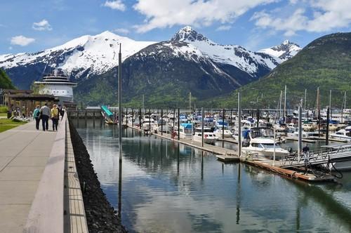 Σκάγκγουέϊ ( Αλάσκα ): Οργανωμένη μαρίνα για μικρά σκάφη, το κρουαζιερόπλοιο σε αναμονή των επιβατών και στο βάθος χιονισμένα βουνά. Καλοκαιρινή φωτογραφία. Σκάγκουέϊ. Αλάσκα. ΗΠΑ.